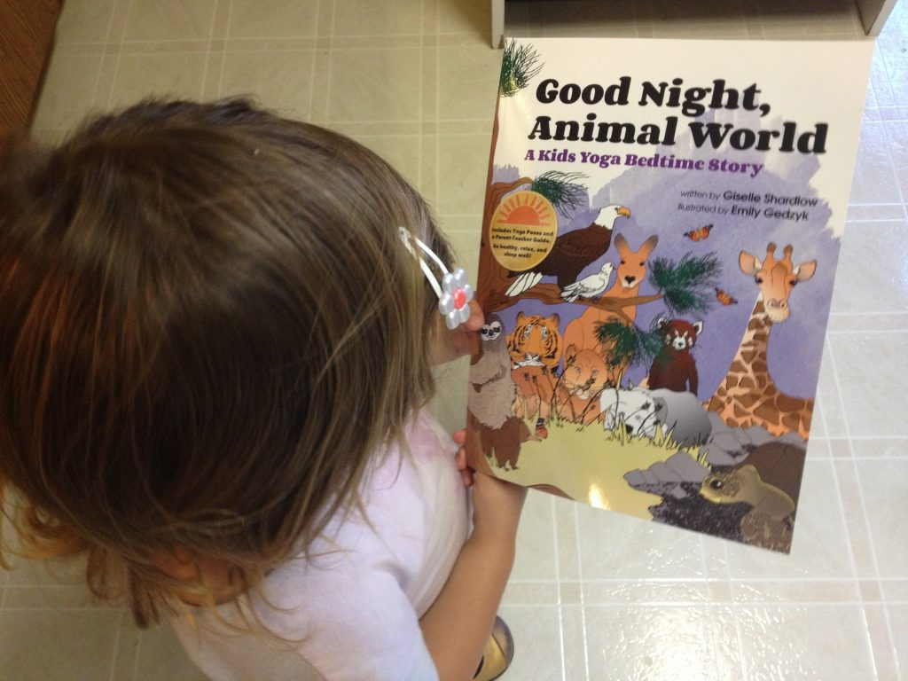 Girl holding Good Night, Animal World yoga book for toddlers | Kids Yoga Stories